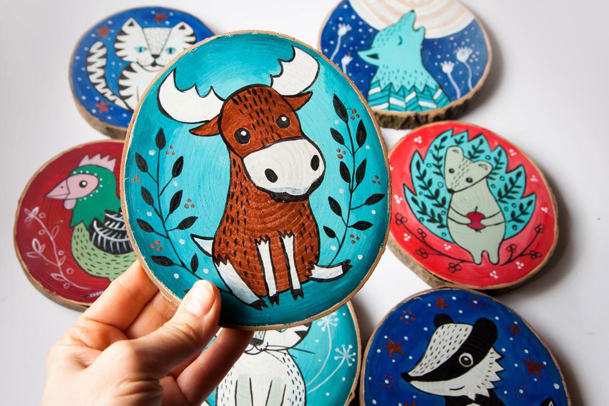 ilustracja zwierząt malowana na drewnianych krążkach