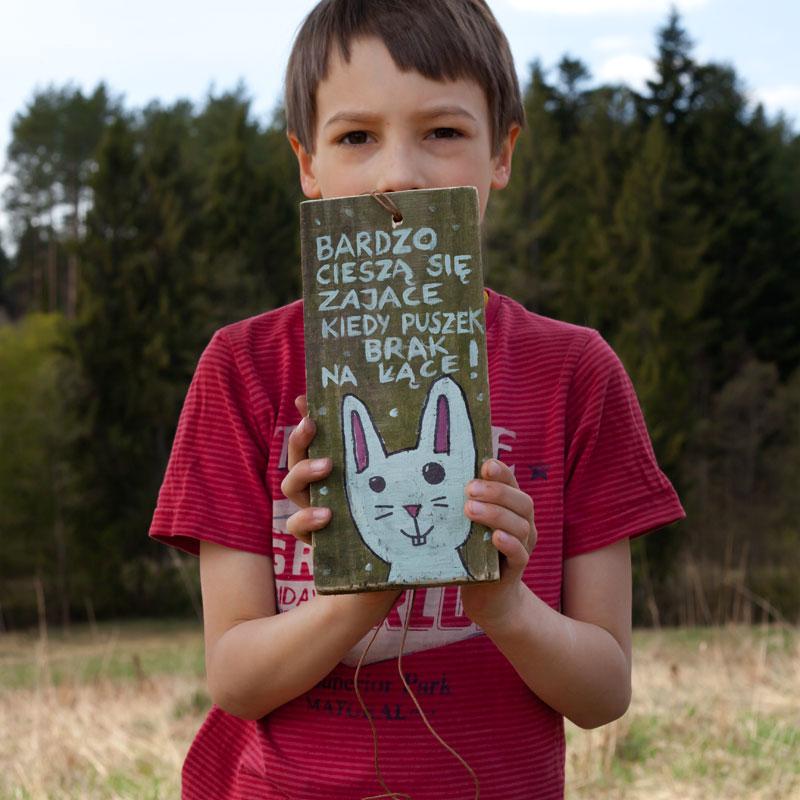 tabliczka z ilustracją i hasłem trzymana przez dziecko
