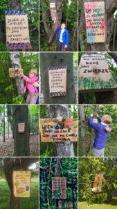 Dzieci wieszające tabliczki informacyjne w lesie