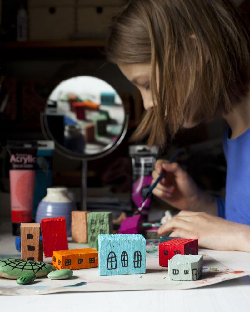 dziecko maluje drewniane domki farbą akrylową